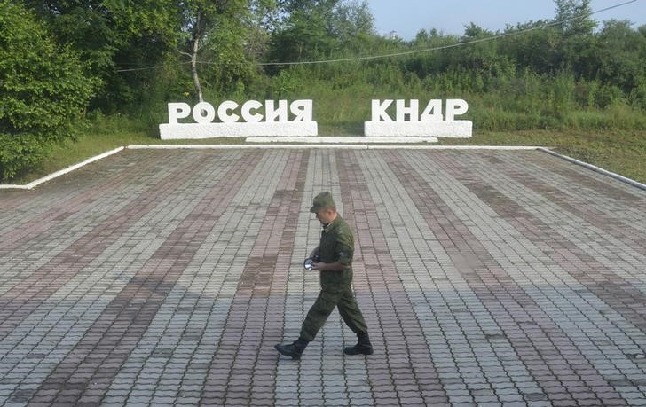 "A guard walks along the platform at the border crossing between Russia and North Korea at the North Korean settlement of Tumangan July 18, 2014. The signage reads, ""Russia"" and ""KNDR (Democratic People's Republic of Korea)"". (Reuters/Yuri Maltsev/File Photo)"