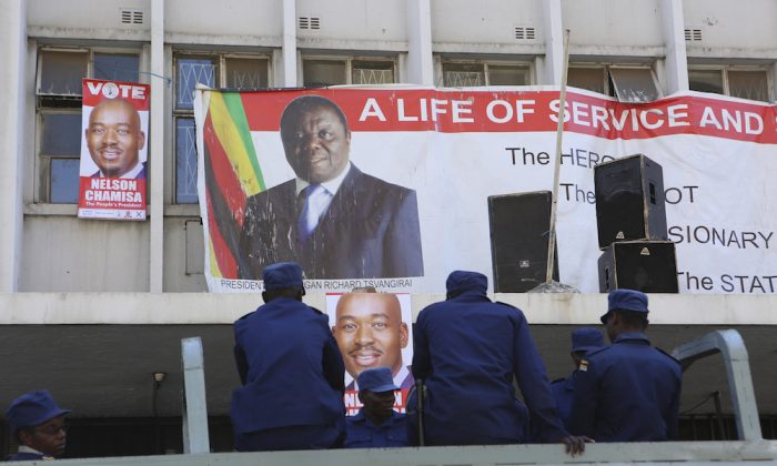 Zimbabwe police are seen outside the  opposition party headquarters in  Harare, Zimbabwe, Aug, 2, 2018. Zimbabwe's President said that his government had been in touch with the main opposition leader in an attempt to ease tensions after election related violence in the capital. (AP Photo/Tsvangirayi Mukwazhi)