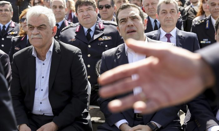 Greece's Prime Minister Alexis Tsipras, right, and Greek public order minister Nikos Toskas attend a ceremony in Athens on March 3, 2018. (Yannis Liakos/InTime News via AP, file)