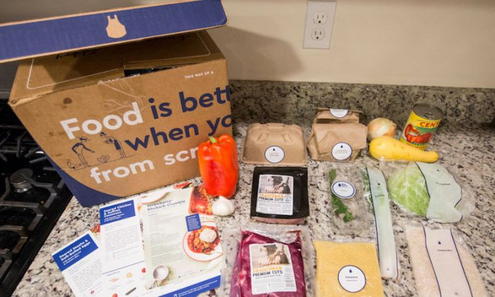 """Items from a """"family-plan"""" Blue Apron box are displayed on a kitchen counter on June 28, 2017 in Boston, Massachusetts. (Scott Eisen/Getty Images)"""