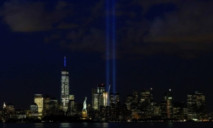 The Tribute in Light is illuminated next to the Statue of Liberty (C), One World Trade Center and the Empire State Building (L) during events marking the 14th anniversary of the 9/11 attacks on the World Trade Center in New York September 11, 2015. (Reuters/Eduardo Munoz)