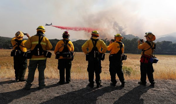 Firefighters watch as an air tanker drops fire retardant to protect homes along the crest of a hill at the River Fire (Mendocino Complex) near Lakeport, California, U.S. Aug. 2, 2018. (Reuters/Fred Greaves)