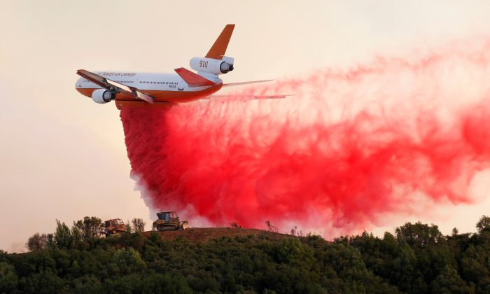 A DC-10 air tanker drops fire retardant along the crest of a hill to protect the two bulldozers below that were cutting fire lines at the River Fire (Mendocino Complex) near Lakeport, California, U.S. Aug. 2, 2018. (Reuters/Fred Greaves)