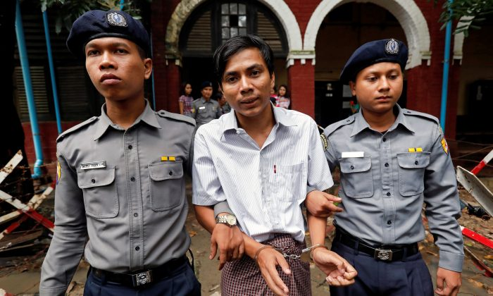 Detained Reuters journalist Kyaw Soe Oo is escorted by police officers as he leaves Insein court in Yangon, Myanmar July 30, 2018. (Reuters/Stringer)