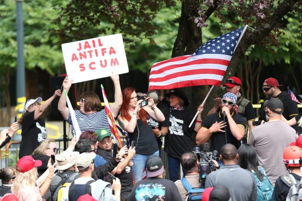 In this June 30, 2018, file photo, the Patriot Prayer group holds a rally and march in Portland, Ore., amid a protest by Antifa groups. Portland is bracing for what could be another round of violent clashes Saturday, Aug. 4, 2018, between a right-wing group holding a rally here and self-described anti-fascist counter-protesters who have pledged to keep Patriot Prayer and other affiliated groups out of this ultra-liberal city. (Mark Graves/The Oregonian via AP, file)