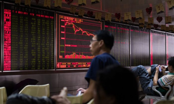 People sit in front of a screen showing stock prices at a brokerage company in Beijing on July 11. (Nicolas Asfouri/AFP/Getty Images)