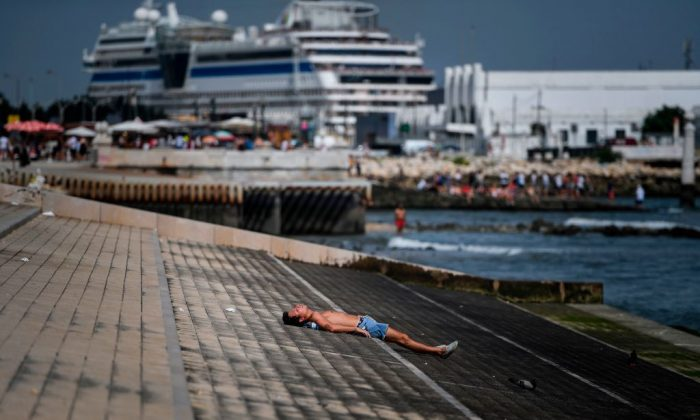 A man sunbathes at Ribeira das Naus in Lisbon on Aug. 3, 2018. (Patrica De Melo Moreira/AFP)