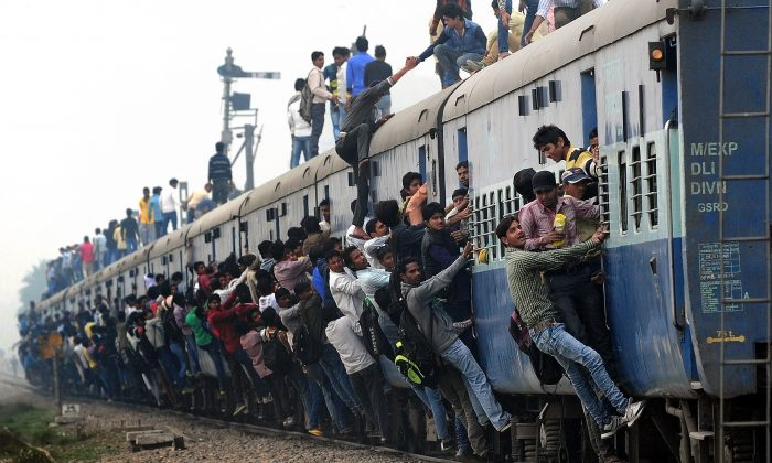 Indian passengers stand and hang onto a train as it departs from a station on the outskirts of New Delhi on February 25, 2015. Since India adopted capitalism, the population has grown and poverty has been reduced. But the government still manages the railway system. (MONEY SHARMA/AFP/Getty Images)