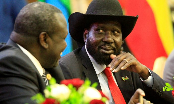 South Sudan's President Salva Kiir (R) talks to South Sudan's rebel leader Riek Machar as they sign a cease fire and power sharing agreement with in Khartoum, Sudan August 5, 2018. (Reuters/Mohamed Nureldin Abdallah)