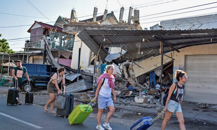 Foreign tourists pull their suitcases as they walk past damaged buildings following a strong earthquake in Pemenang, North Lombok, Indonesia  Aug. 6, 2018. (Reuters)