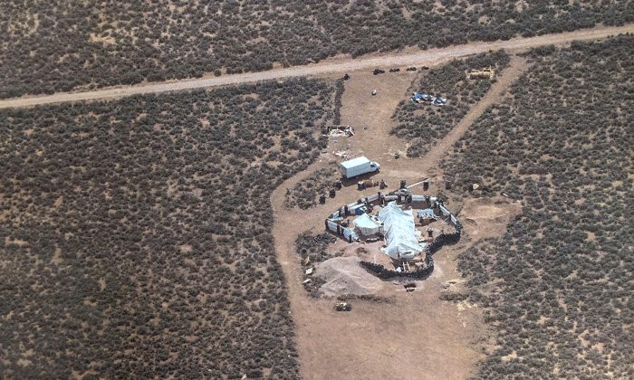Aerial photo released by Taos County Sheriff's Office shows a rural compound during an unsuccessful search for a missing 3-year-old boy in Amalia on Aug. 3, 2018. (Taos County Sheriff's Office via AP)