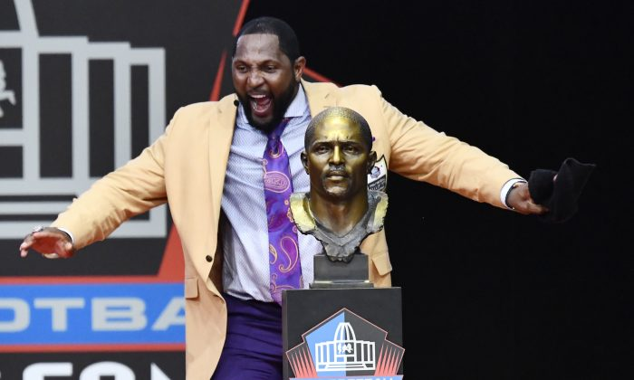 Former Baltimore Ravens linebacker Ray Lewis dances beside his bust. Aug. 4, 2018, in Canton, Ohio. (AP Photo/David Richard)