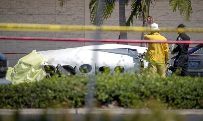Santa Ana fire and police and Orange County Fire departments respond to the scene of a deadly plane crash in a parking lot near South Coast Plaza in Santa Ana, Calif., on Sunday, Aug. 5, 2018. (Allen J. Schaben /Los Angeles Times via AP)