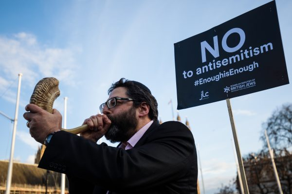 A protester blows through a shofar during a demonstration in Parliament Square against anti-Semitism in the Labour Party on March 26, 2018 in London, England. (Jack Taylor/Getty Images)