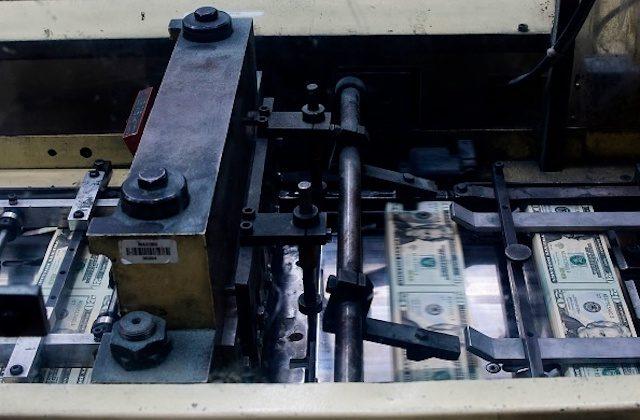 Sheets of freshly printed 20 USD notes cut into bills before bundling at the US Treasury's Bureau of Engraving and Printing in Washington, DC July 20, 2018. (EVA HAMBACH/AFP/Getty Images)