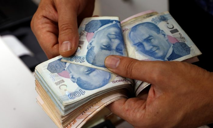 A money changer counts Turkish lira banknotes at a currency exchange office in Istanbul, Turkey, on Aug. 2, 2018. (Reuters/Murad Sezer)