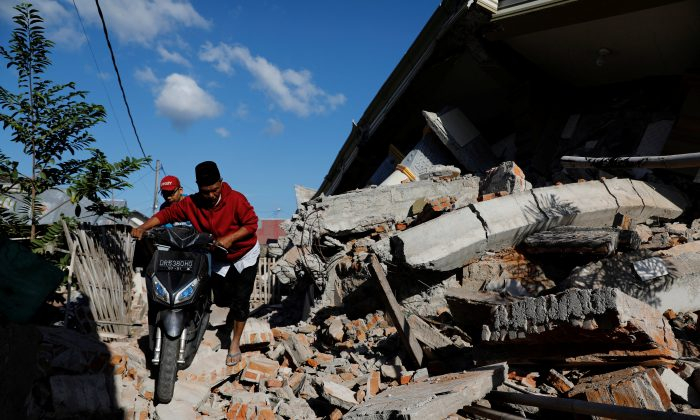 People push their motorcycle through the collapsed ruins of a mosque after an earthquake hit on Sunday in Pemenang, Lombok island, Indonesia, August 7, 2018. (Reuters/Beawiharta)