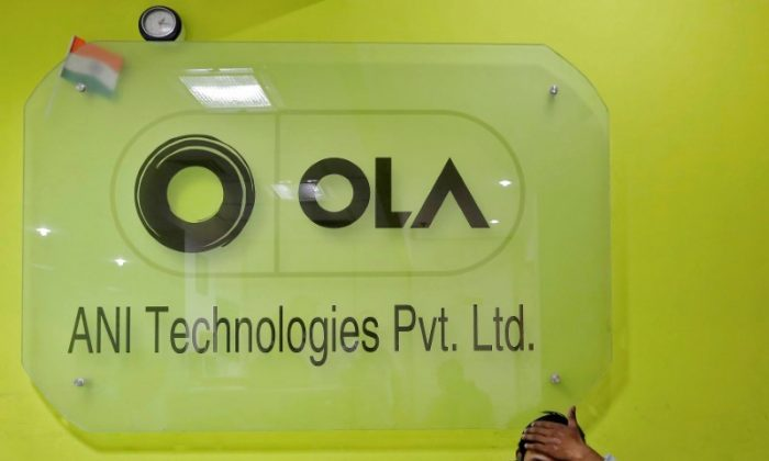 An employee speaks over his phone as he sits inside the office of Ola cab service on the outskirts of New Delhi, India, on April 20, 2016. (REUTERS/Anindito Mukherjee)