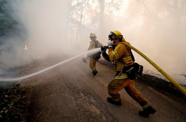 FILE PHOTO: A firefighter knocks down hotspots to slow the spread of the River Fire (Mendocino Complex) in Lakeport, California, U.S. July 31, 2018. (Reuters/Fred Greaves/File Photo)