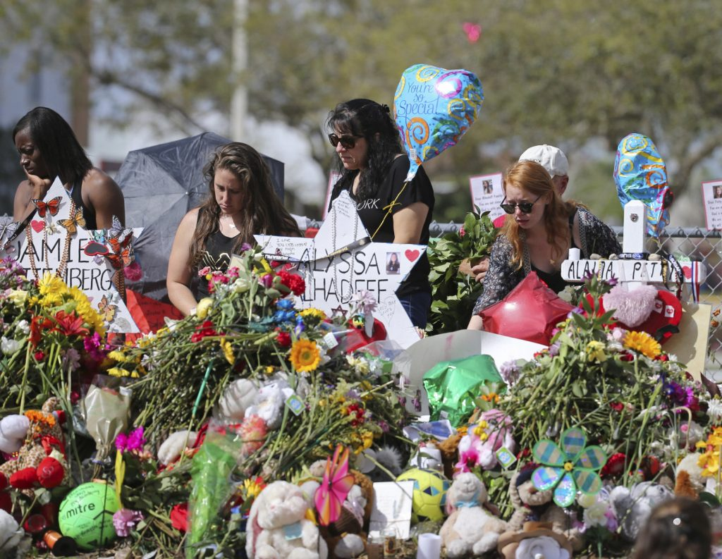 Mourners bring flowers as they pay tribute at a memorial for the victims of the shooting at Marjory Stoneman Douglas High School in Parkland, Fla., on Sunday, Feb. 25, 2018. (David Santiago/Miami Herald via AP)