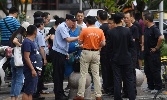 A police officer speaks with a P2P petitioner (C) as security personnel (R) look on, near China's Banking Regulatory Commission office in Beijing on Aug. 6, 2018. (Greg Baker/AFP/Getty Images)