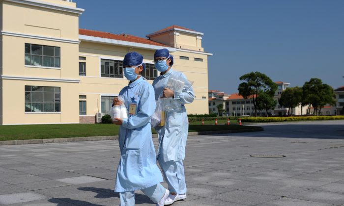 Nurses walk in front of an isolation hospital in southwest Shanghai on May 14, 2013. (Peter Parks/AFP/Getty Images)