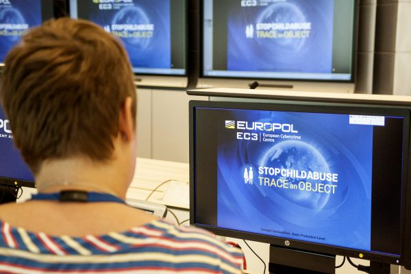 A Europol police agent looks at the onscreen logo of a new website launched by Europol. Europe's police agency launched the new website, which shows everyday objects found in the background of child sex abuse images, in the hope that it will lead police around the world to victims and help arrest perpetrators. (JAN HENNOP/AFP/Getty Images)
