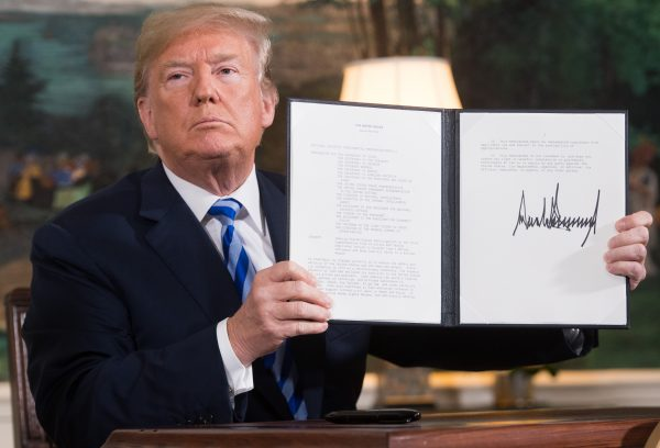 U.S. President Donald Trump signs a document reinstating sanctions against Iran after announcing the U.S. withdrawal from the Iran Nuclear deal, in the Diplomatic Reception Room at the White House in Washington, DC, on May 8, 2018. (SAUL LOEB/AFP/Getty Images)