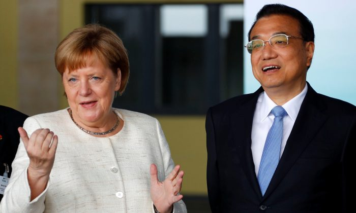 German Chancellor Angela Merkel (L) and Chinese Premier Li Keqiang arrive for a presentation of self-driving cars at the defunct historic Tempelhof Airport in Berlin, on July 10, 2018. (FABRIZIO BENSCH/AFP/Getty Images)