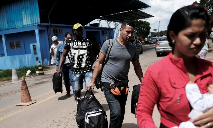 Venezuelans walk to show their passports or identity cards at the Pacaraima border control, Roraima state, Brazil November 16, 2017. (Reuters/Nacho Doce/File photo)