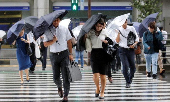 Passersby using umbrellas struggle against a heavy rain and wind as Typhoon Shanshan approaches Japan's mainland in Tokyo, Japan Aug. 8, 2018. (Reuters/Toru Hanai)