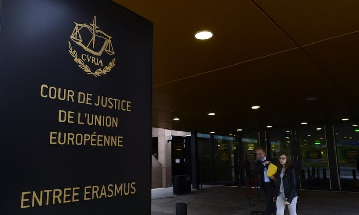 People walk away from the entrance of the European Court of Justice (SCJ) in Luxembourg, on Oct. 5, 2015. (Photo credit should read JOHN THYS/AFP/Getty Images)