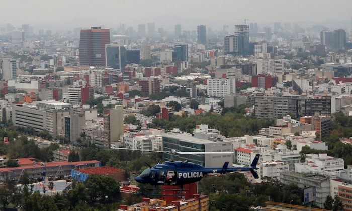 """Police officers, members of a team known as """"Condores"""", stand by the door of the helicopter during a patrol of the city, part of a new strategy to combat the crime in Mexico City, Mexico Aug. 3, 2018. (REUTERS/Carlos Jasso)"""