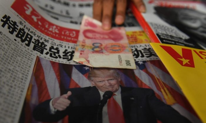 A vendor picks up a 100 yuan note above a newspaper featuring a photo of US president-elect Donald Trump, at a news stand in Beijing on Nov. 10, 2016. (GREG BAKER/AFP/Getty Images)