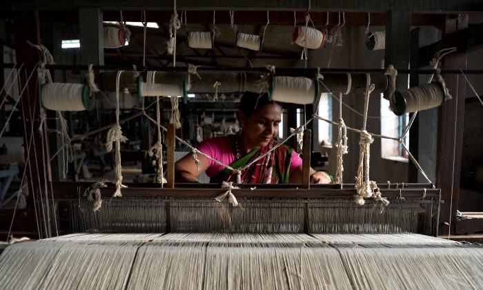 An employee at a flag-making company weaves cotton yarn in Tulasigeri village in the southern state of Karnataka, India, on May 9, 2018.  (Manjunath Kiran/AFP/Getty Images)