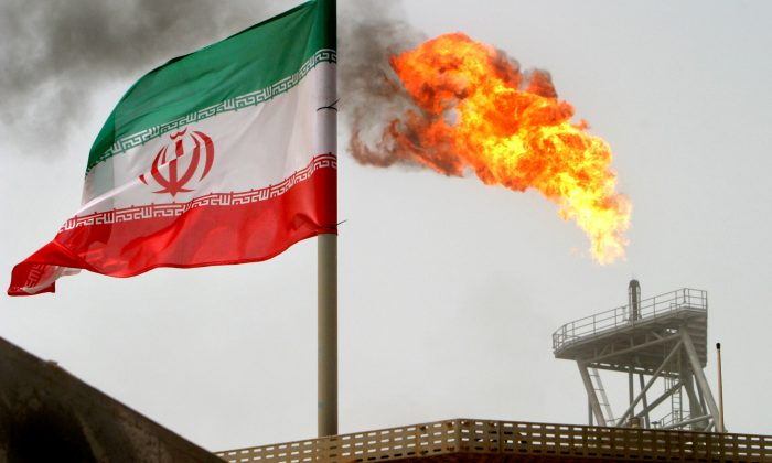 A gas flare on an oil production platform in the Soroush oil fields is seen alongside an Iranian flag in the Persian Gulf, Iran, July 25, 2005. (Reuters/Raheb Homavandi)