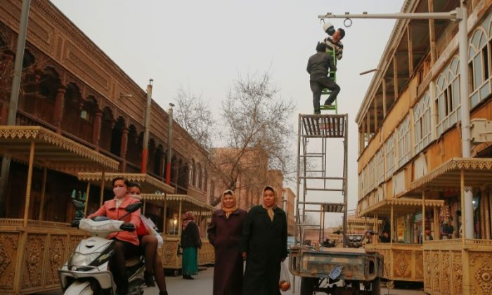 Men install a CCTV camera in a shopping street in the old town of Kashgar, in the Xinjiang region of China on March 23, 2017. (Reuters/Thomas Peter)