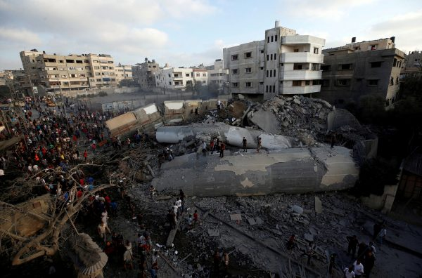 Palestinians stand around the rubble of a building bombed by Israeli forces in retaliation to multiple missile attacks on Israel by Hamas terrorists