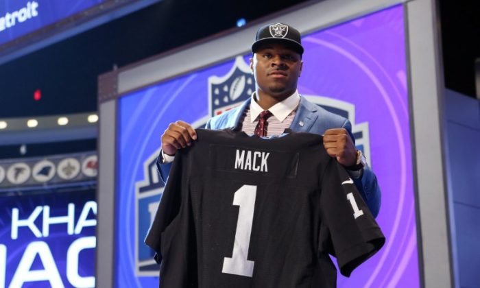 Khalil Mack holds up a jersey after being selected as the number five overall pick in the first round of the NFL Draft to the Oakland Raiders at Radio City Music Hall on May 8, 2018. (Adam Hunger/USA Today Sports)