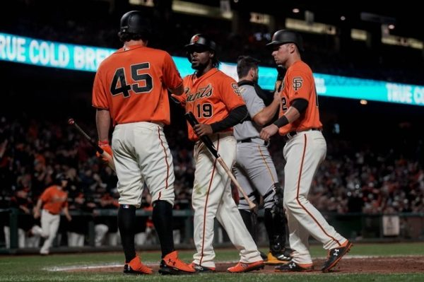 San Francisco Giants starting pitcher Derek Holland and second baseman Alen Hanson and second baseman Joe Panik celebrate against the Pittsburgh Pirates during the fourth inning.