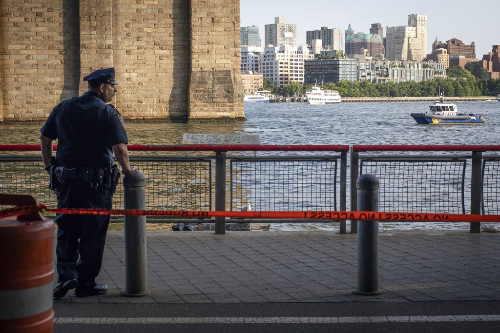 A New York Police Department officer stands guard as authorities investigate the death of a baby boy who was found floating in the East River near the Brooklyn Bridge in the Manhattan borough of New York on Aug. 5, 2018. (AP Photo/Robert Bumsted, File)