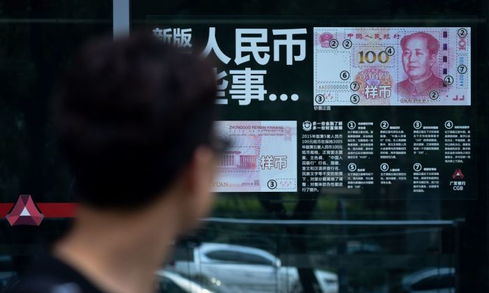 A man looks at currency information posted on the window of a bank in Beijing on July 20, 2018. (Wang Zhao/AFP/Getty Images)