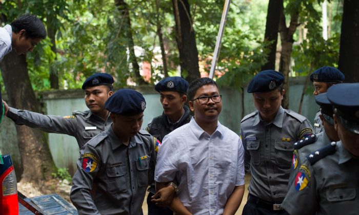 Detained Myanmar journalist Wa Lone arrives in handcuffs escorted by police to a courtroom for his on going trial in Yangon on July 23, 2018. -Two Reuters journalists in Myanmar, Wa Lone, 32, and Kyaw Soe Oo, 28, were arrested while investigating a massacre of Rohingya Muslims. (YE AUNG THU/AFP/Getty Images)