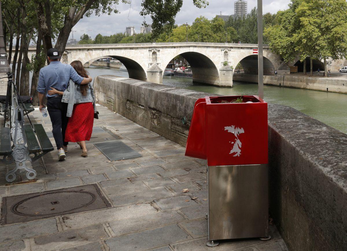 A couple walks near an eco-friendly urinal