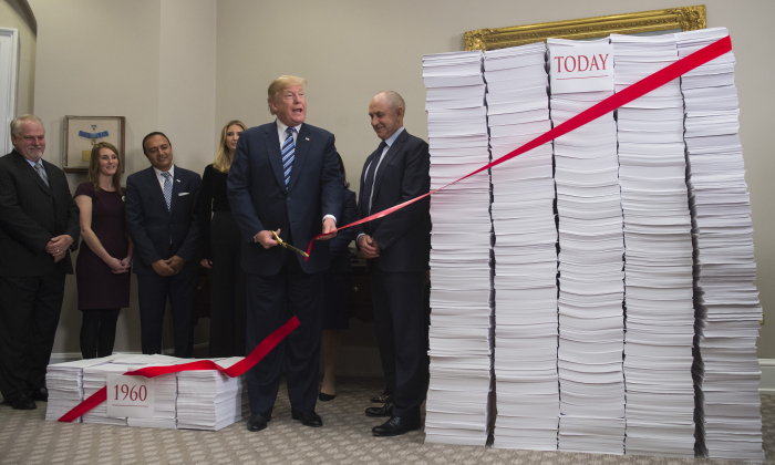 President Donald Trump cuts a red tape tied between two stacks of papers representing the government regulations of the 1960s (L) and the regulations of today (R) after he spoke about his administration's efforts in deregulation in the Roosevelt Room of the White House in Washington on Dec. 14, 2017. (Saul Loeb/AFP/Getty Images)