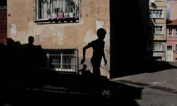 A boy runs down a dark alleyway. (Unsplash)