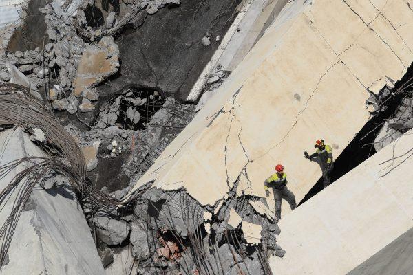 Rescuers scour rubble of the collapsed bridge for survivors
