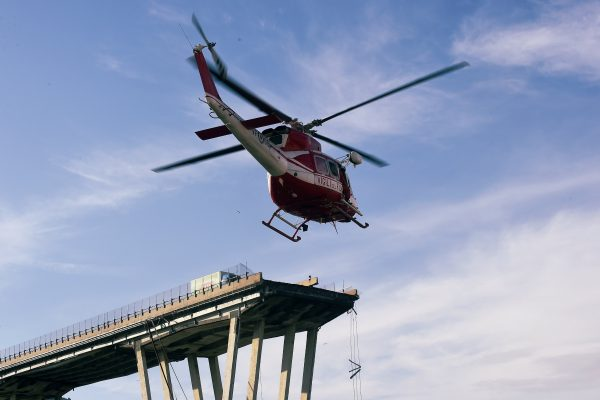 A rescue helicopter hovers above collapsed Morandi bridge