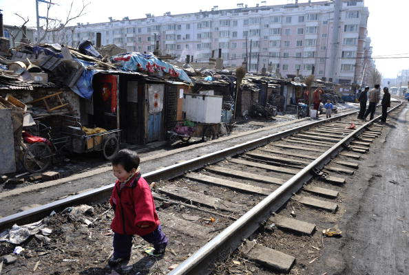 A child plays along a railway at a shanty town where residents will move into low-rent apartments provided by the government on March 11, 2009 in Shenyang of Liaoning Province, China. (China Photos/Getty Images)