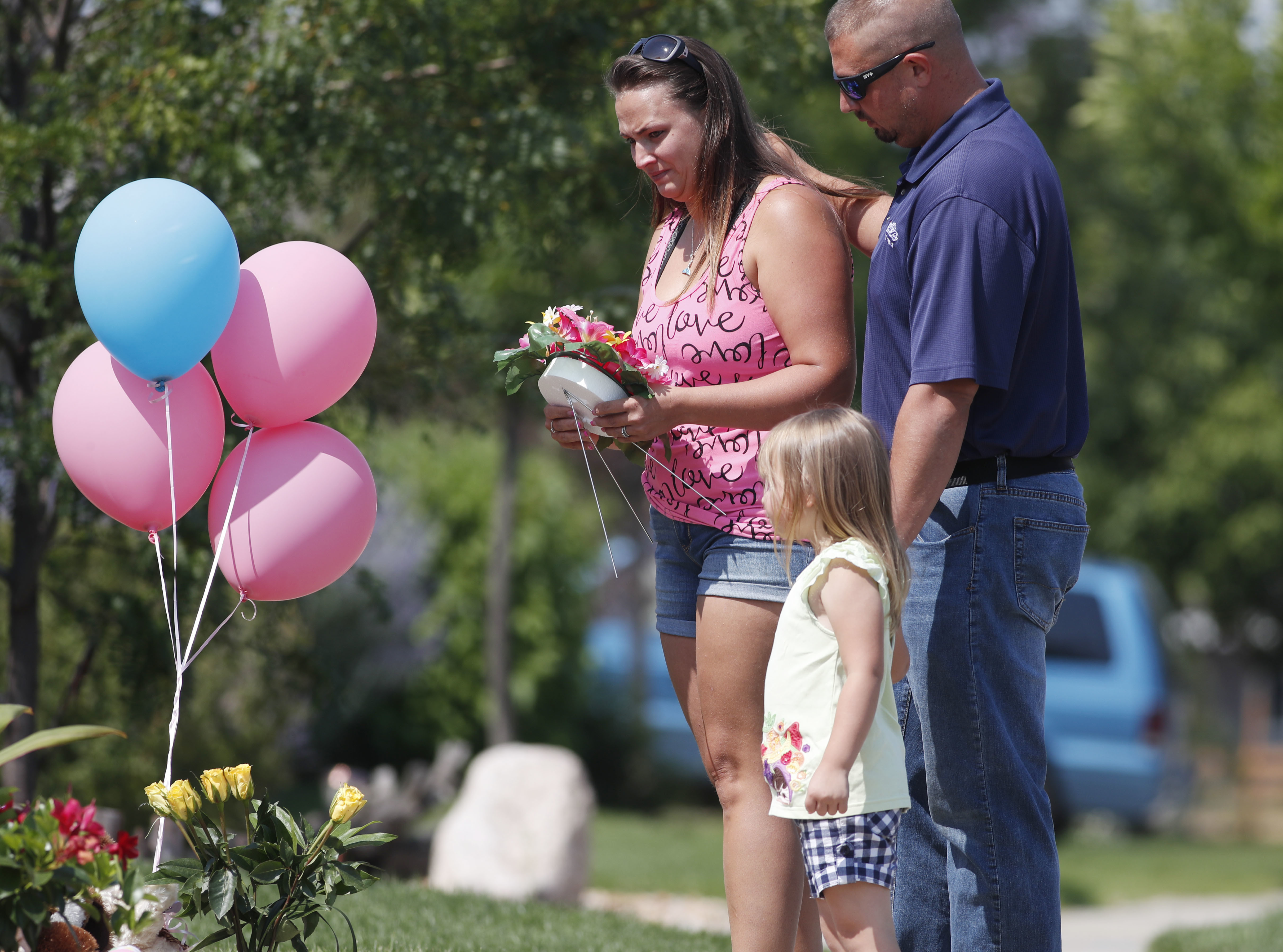 Ashley Bell, left, is consoled by her husband, Steven, and 4-year-old daughter Liberty as the woman places a tribute outside the home where a pregnant woman and her two daughters lived in Frederick, Colorado on Aug. 16, 2018. (AP Photo/David Zalubowski)